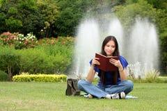 Nätt ung kvinna som läser en bok på parken royaltyfri fotografi