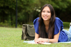 Nätt ung kvinna som läser en bok på parken arkivbild