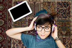 Nätt ung kvinna som ligger med hörlurar och minnestavlan Arkivbilder
