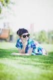 Nätt ung kvinna som ligger på den gröna gräsmattan Royaltyfri Fotografi