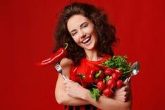 Nätt ung kvinna som poserar med den nya röda gaffeln och skeden för persilja för grönsallat för sidor för gräsplan för peppar för fotografering för bildbyråer
