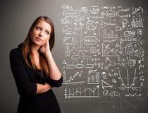 Nätt kvinna som ser aktiemarknadgrafer och symboler Arkivbilder