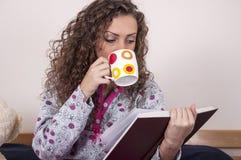 Nätt ung kvinna som sitter på underlaget Arkivbilder
