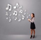 Nätt ung kvinna som sjunger och lyssnar till musik med musikal n fotografering för bildbyråer