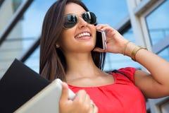 Nätt ung kvinna som talar på smartphonen Arkivbild
