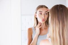 Nätt ung kvinna som trycker på hennes framsida, medan se spegeln, skönhetbegrepp, hudomsorg, plastikkirurgi royaltyfri fotografi