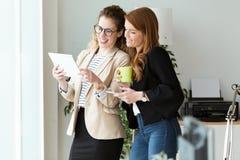 Nätt ung kvinna som två använder hennes digitala minnestavla i kontoret arkivfoton