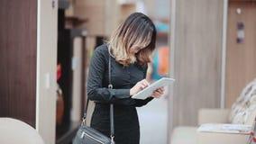 Nätt ung kvinna som väljer det högra möblemanget för hennes lägenhet i ett modernt lager för hem- inredningar