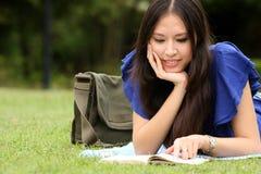Nätt ung kvinnaavläsning henne bok royaltyfri fotografi