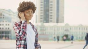Nätt ung kvinnlig, i sång och att sjunga för hörlurar lyssnande favorit- utomhus lager videofilmer