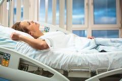Nätt, ung kvinnlig patient i ett modernt sjukhusrum Royaltyfri Fotografi
