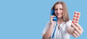 Nätt ung läkare som talar på telefonen royaltyfri bild