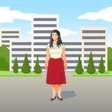 Nätt ung Latino kvinna i ett stilfullt rött kjolanseende som ler i gatan stock illustrationer