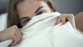 Nätt ung lycklig caucasian kvinna för stående med olika kulöra ögon som ligger i säng i morgonen som täcker hennes framsida stock video