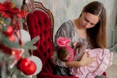Nätt ung mamma för glad jul som och för lyckliga ferier inomhus läser en bok till hennes gulliga dotter nära julgranen arkivfoto