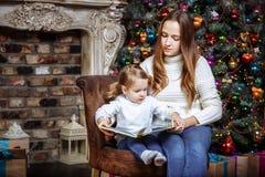 Nätt ung mamma som inomhus läser en bok till hennes gulliga dotter nära julgranen royaltyfri foto