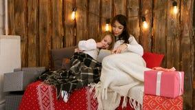 Nätt ung mamma som läser en julsaga till hennes gulliga dottersammanträde på soffan som slås in i filtar fotografering för bildbyråer