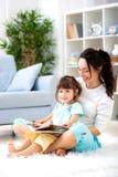 Nätt ung moder som läser en bok till hennes dotter som sitter på mattan på golvet i rummet Läsa med barn royaltyfria foton
