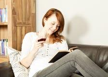 Nätt ung rödhårig mankvinna som läser en bok Royaltyfri Fotografi