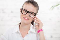 Nätt ung sekreterare på telefonen arkivbild