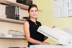 Nätt ung sekreterare som använder en kopieringsmaskin Arkivbilder