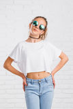 Nätt ung sexig modekvinna som poserar på den vita tegelstenväggen Arkivfoton