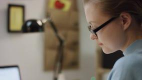 Nätt ung student som gör läxa vid tabellen lager videofilmer