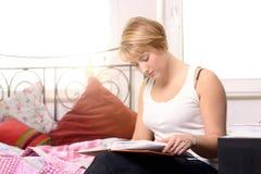 Nätt ung studentläsning i en lärobok Arkivfoto