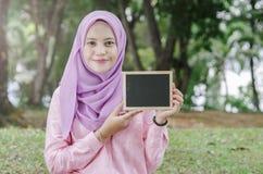 Nätt ung upphetsad kvinna som rymmer den tomma tomma svart tavlan för text Royaltyfri Foto