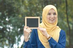 Nätt ung upphetsad kvinna som rymmer den tomma tomma svart tavlan för text Royaltyfria Bilder