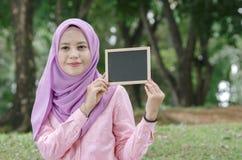 Nätt ung upphetsad kvinna som rymmer den tomma tomma svart tavlan för text Royaltyfri Fotografi