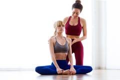 Nätt ung yogainstruktör som hemma hjälper hennes student i en yogaperiod Baddha Konasana poserar royaltyfria bilder