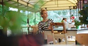 Nätt ungt caucasian flickasammanträde på det friakafét och vänta på någon Arkivbilder