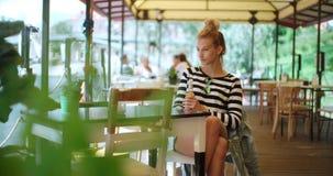 Nätt ungt caucasian flickasammanträde på det friakafét och vänta på någon Fotografering för Bildbyråer