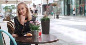 Nätt ungt caucasian flickasammanträde på kafét och le till en kamera Arkivfoto