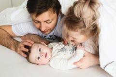 Nätt yong familj i säng arkivbild