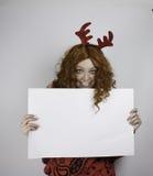 Nätta bärande horn på kronhjort för ung kvinna och tomt tecken för innehav Royaltyfri Foto