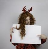 Nätta bärande horn på kronhjort för ung kvinna och tomt tecken för innehav Royaltyfria Bilder