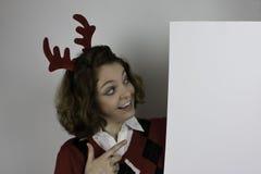 Nätta bärande horn på kronhjort för ung kvinna och tomt tecken för innehav Royaltyfri Bild