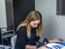 Nätta blonda konstnärattraktioner med hennes tatuering bearbetar med maskin en tatuering på t Arkivbild
