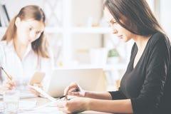 Nätta businessladies som gör skrivbordsarbete Fotografering för Bildbyråer