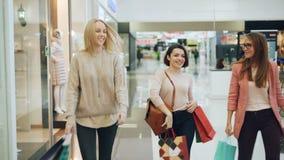 Nätta flickavänner har gyckel i shoppinggalleria som omkring dansar och vänder med pappers- påsar, att le och att skratta stock video