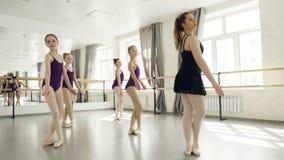 Nätta flickor i body gör plie och beväpnar förehavanden med läraren under balettkurs i ljus studio arkivfilmer