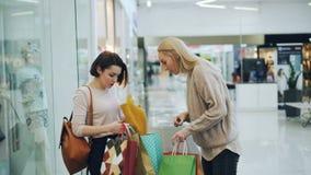 Nätta flickor möter i shoppinggalleria, visar köp i pappers- påsar och diskuterar priser och att bekläda stock video