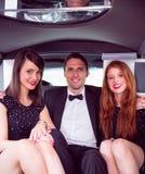 Nätta flickor med dammannen i limousineet Arkivbilder