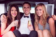 Nätta flickor med dammannen i limousineet Royaltyfri Fotografi