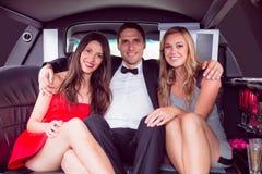 Nätta flickor med dammannen i limousineet Arkivfoto