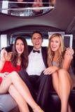 Nätta flickor med dammannen i limousineet Arkivbild