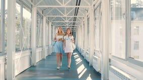 Nätta flickor som går över den långa korridoren stock video