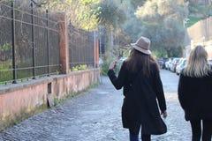 Nätta flickor som går i gatan arkivfoton
